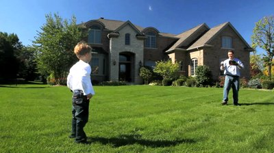 stock-footage-a-father-and-young-son-play-catch-in-front-of-their-luxury-home