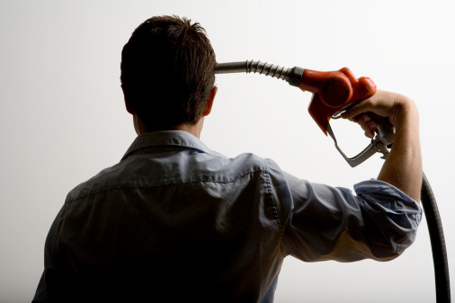 Man holding gasoline pump to head, rear view